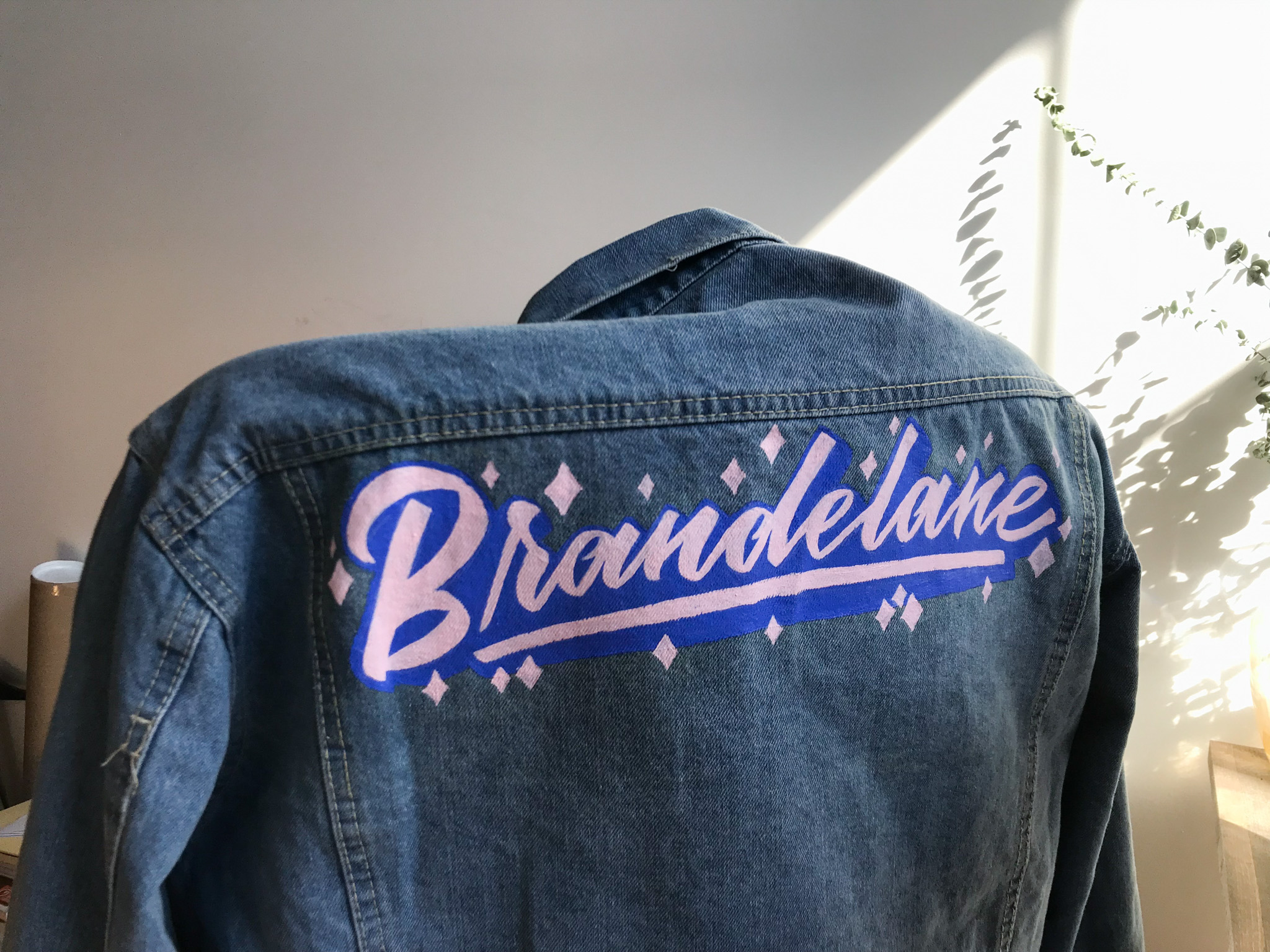 Hand painted custom lettering on denim jacket for Brandelane by Hillery Powers
